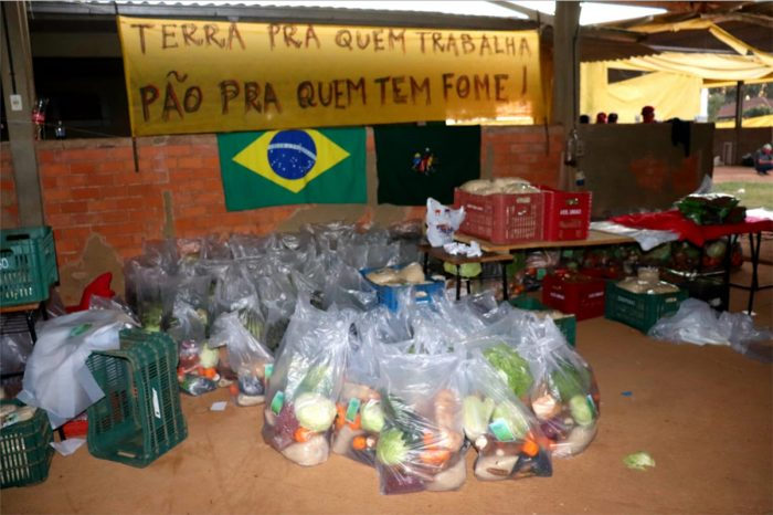 """Food donations from the MST in Brazil. The banner reads: """"Land for those who work, bread for those who are hungry."""" (Photo by Thea Tavares)"""