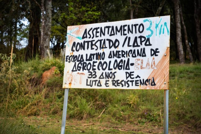 """A sign reading """"Contested settlement / Lapa Latin American School of Agroecology, 33 years of struggle and resistance"""" (Photo by Rafael Forsetto)"""