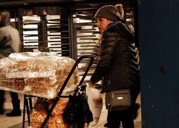 A new york city street food vendor sells pastries outside the subway station