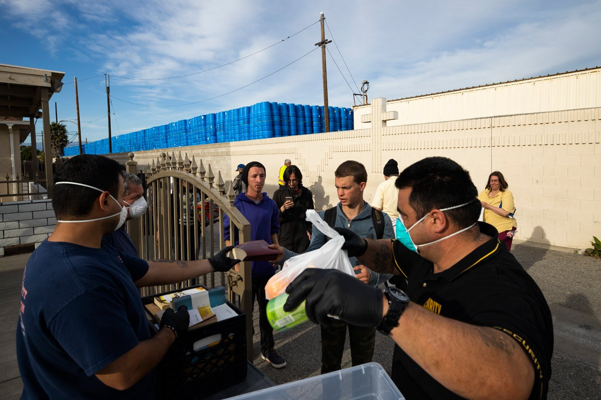 Ventura County Rescue Mission workers hand out food packages to the homeless on March 31, 2020 in Ventura, California.