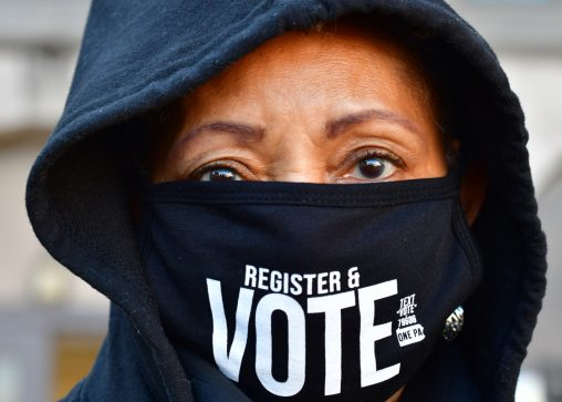 """Site manager Eileen Bowman wears a """"REGISTER & VOTE"""" mask as long lines of voters wait to cast early voting ballots at Roxborough High School on October 17, 2020 in Philadelphia, Pennsylvania. (Photo by Mark Makela/Getty Images)"""