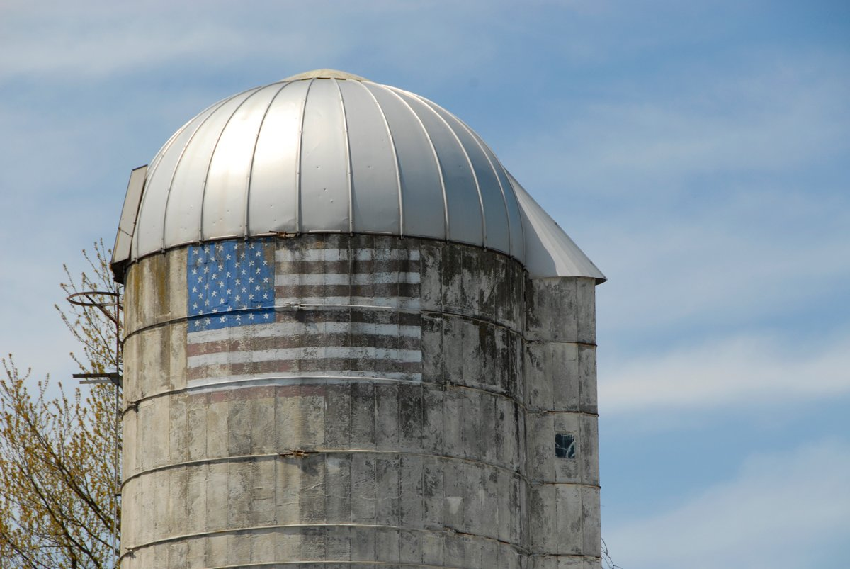 a weathered silo with a US flag painted on it