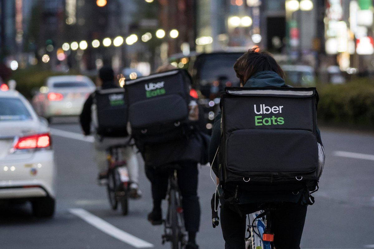Uber Eats food delivery app riders lining up in the street to deliver food from restaurants