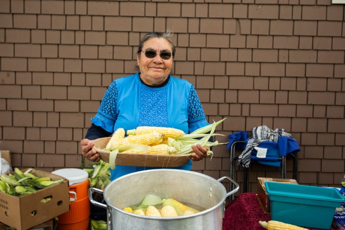 Doña Toña holding ears of freshly harvested corn to make elote. (Photo credit: Gorge Grown)