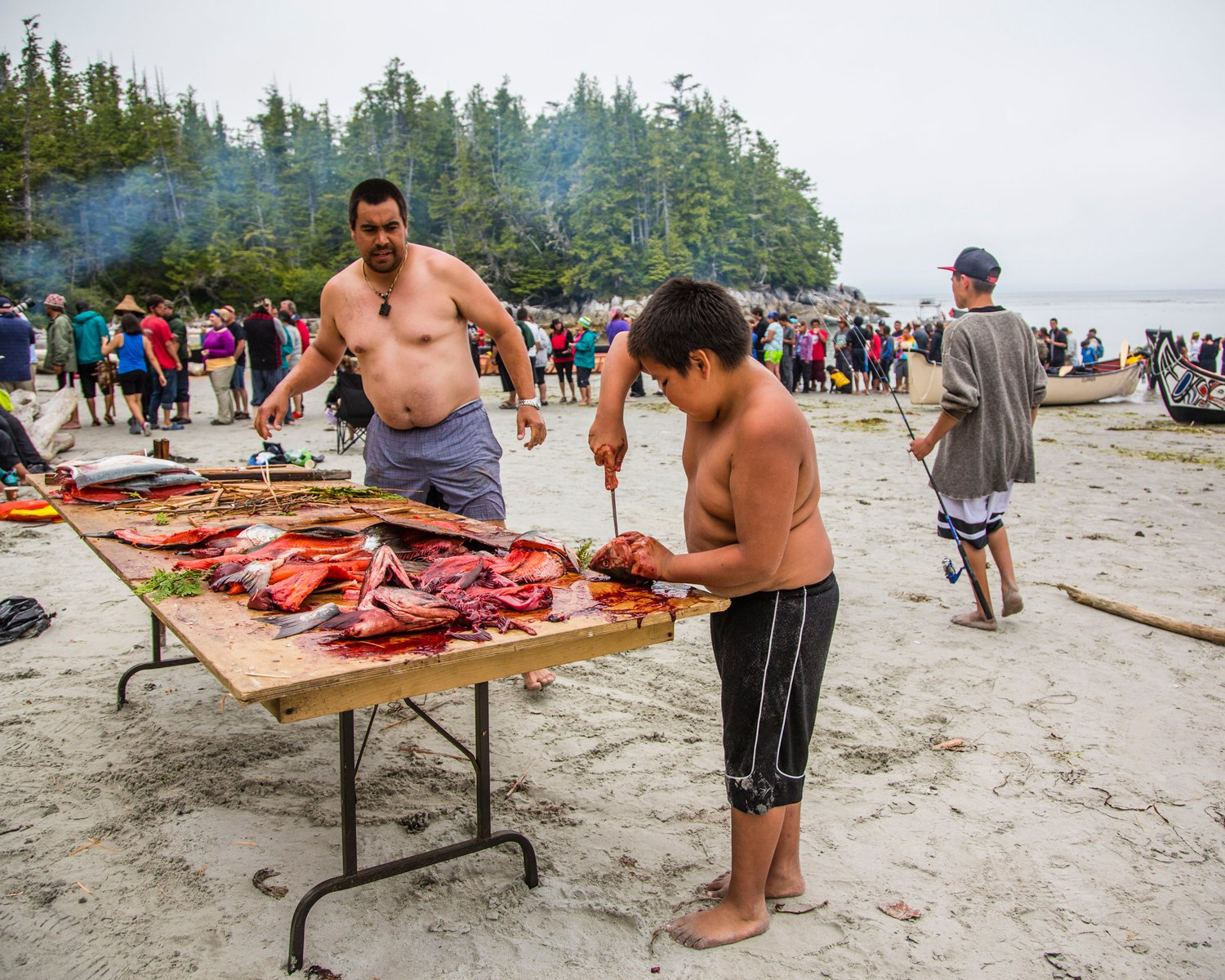 Two members of the Wuikinuxv First Nation prepare wild salmon to feed to guests to their territory during the annual Tribal Canoe Journey, which brings together First Nations from across the Pacific Northwest.
