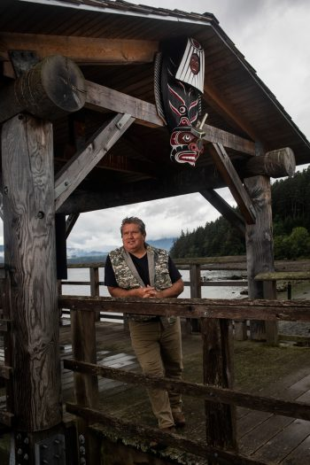 Ho'miska̱nis, Don Svanvik, a traditional carver, and hereditary chief and current elected Chief of Council of the 'Na̱mg̱is First Nation under a carving he made on the waterfront in Alert Bay.