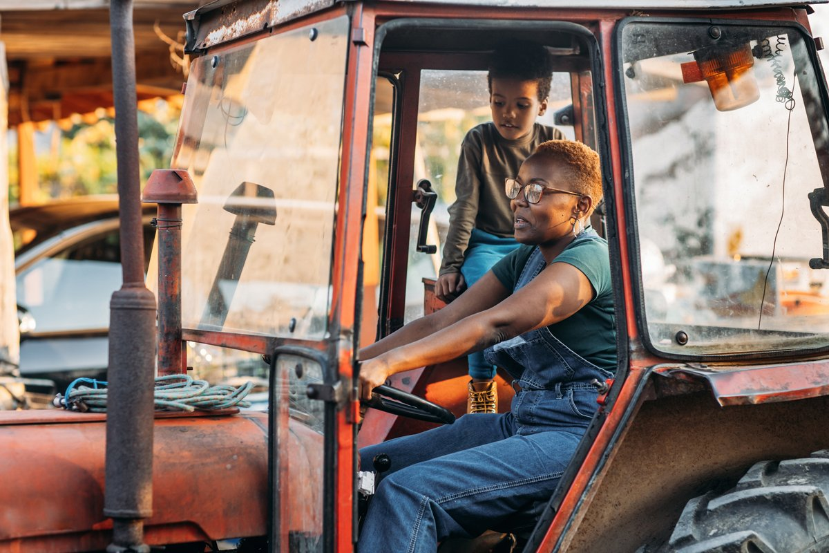 A Black farmer and a child drive a tractor on the farm.