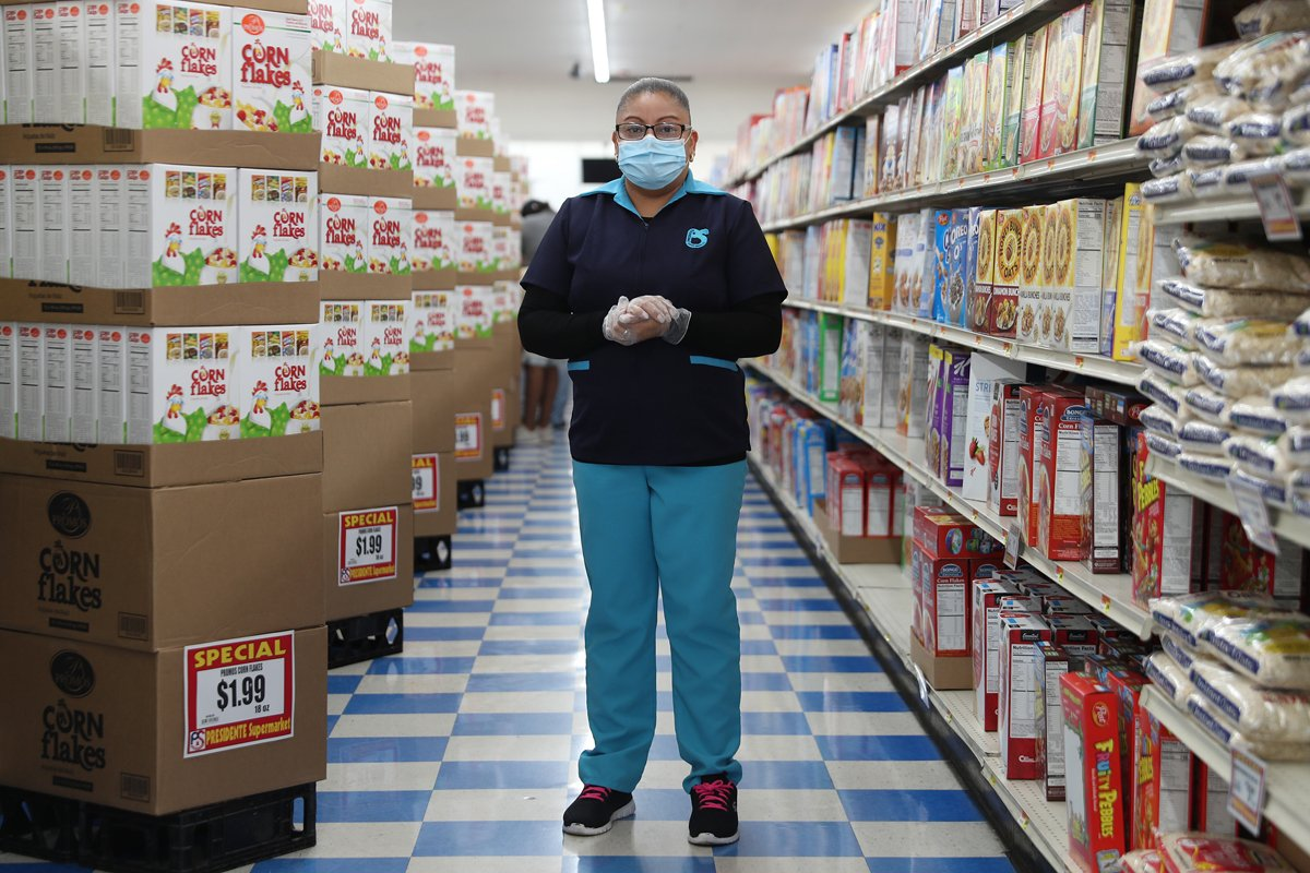A frontline supermarket worker poses for a picture as she wears a mask and gloves while working at a Miami supermarket.