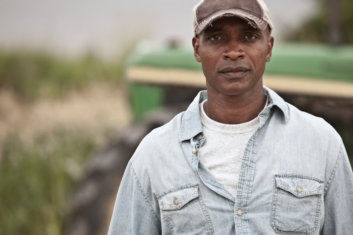 a black farmer standing in front of a tractor.