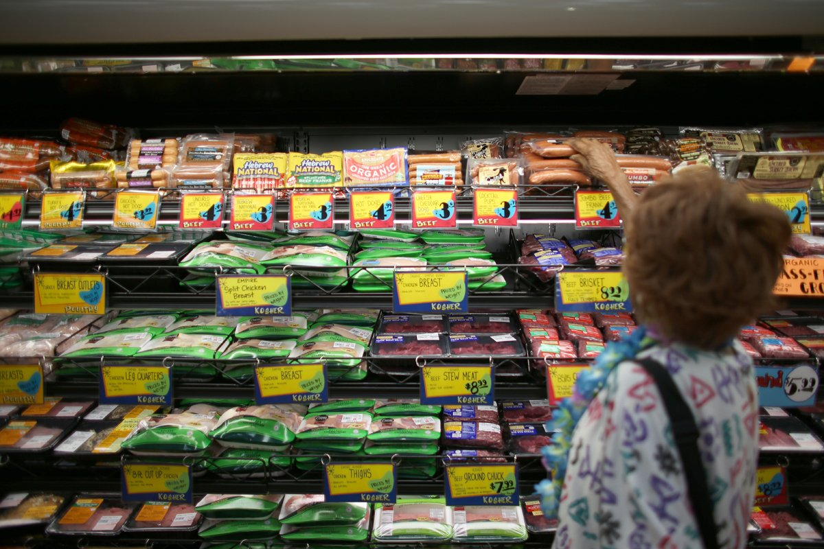 shopper inspecting certified meats for their humanewashing labels