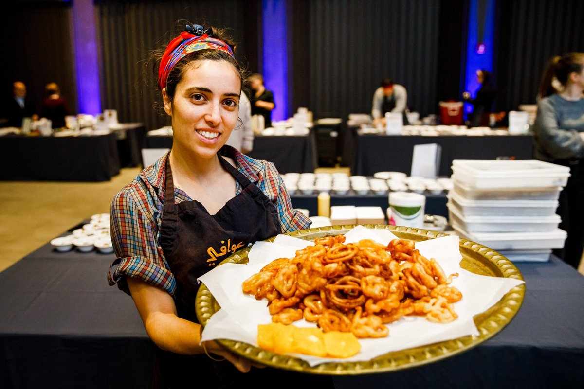 Annabel Rabiyah holding a platter of zangula at a Jewish food festival