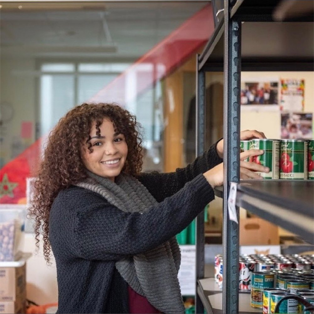 A Swipe Out Hunger worker stocks the shelves at a campus food pantry.
