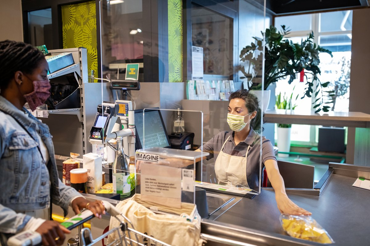 A grocery worker behind plexiglas and with masks during covid