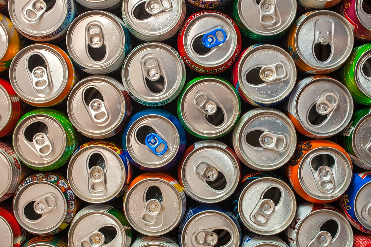 A photo of a bunch of soda cans from above, representing big food and junk food