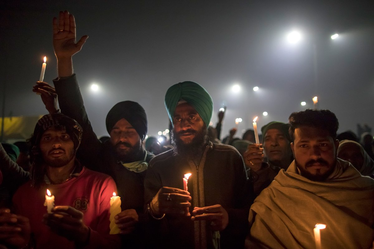 Farmers participate in a candlelight vigil on New Year's Eve on a highway leading to Delhi on the Gaziabad border on December 31, 2020 in Delhi, India. (Photo by Anindito Mukherjee/Getty Images)