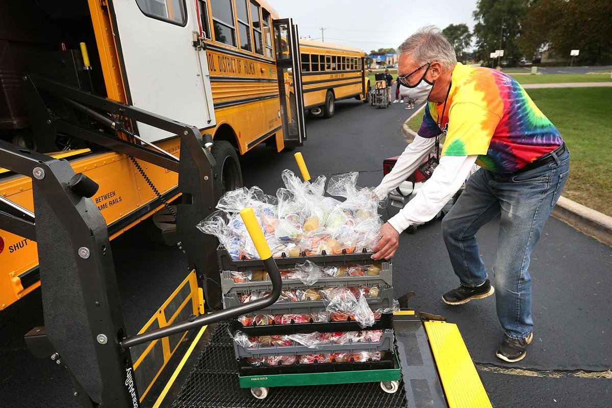A Holmen School District transportation employee loads lunches onto a school bus before helping deliver them throughout the community.