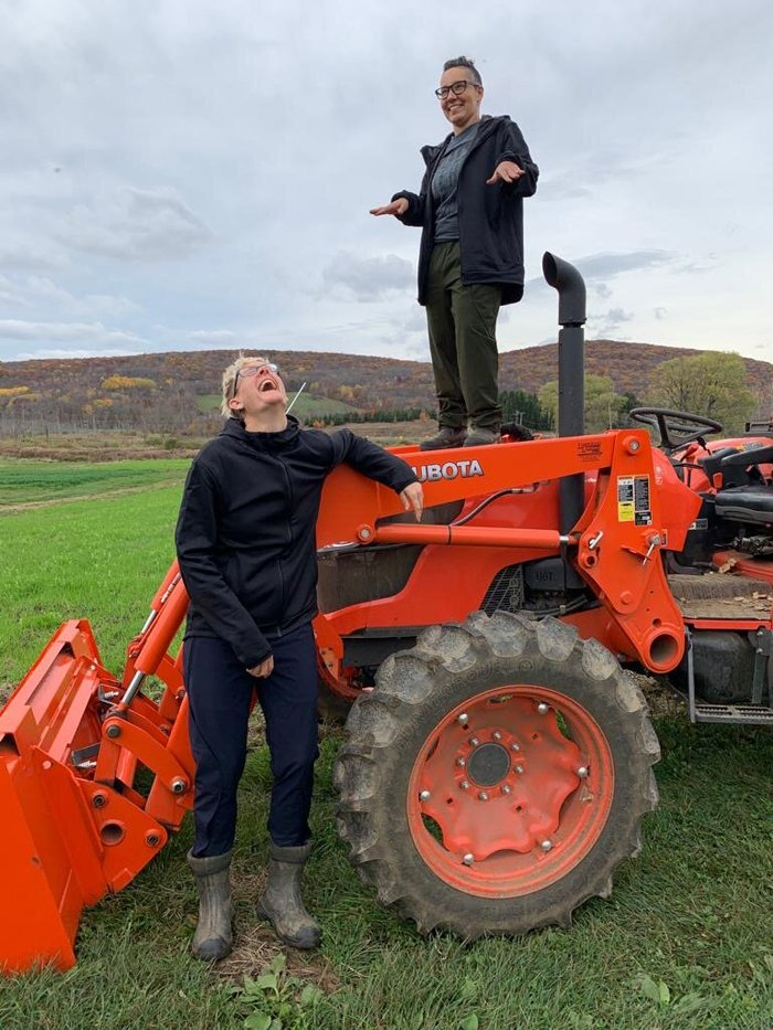 Maggie Cheney (left) and D Rooney on a tractor at Rock Steady Farm.
