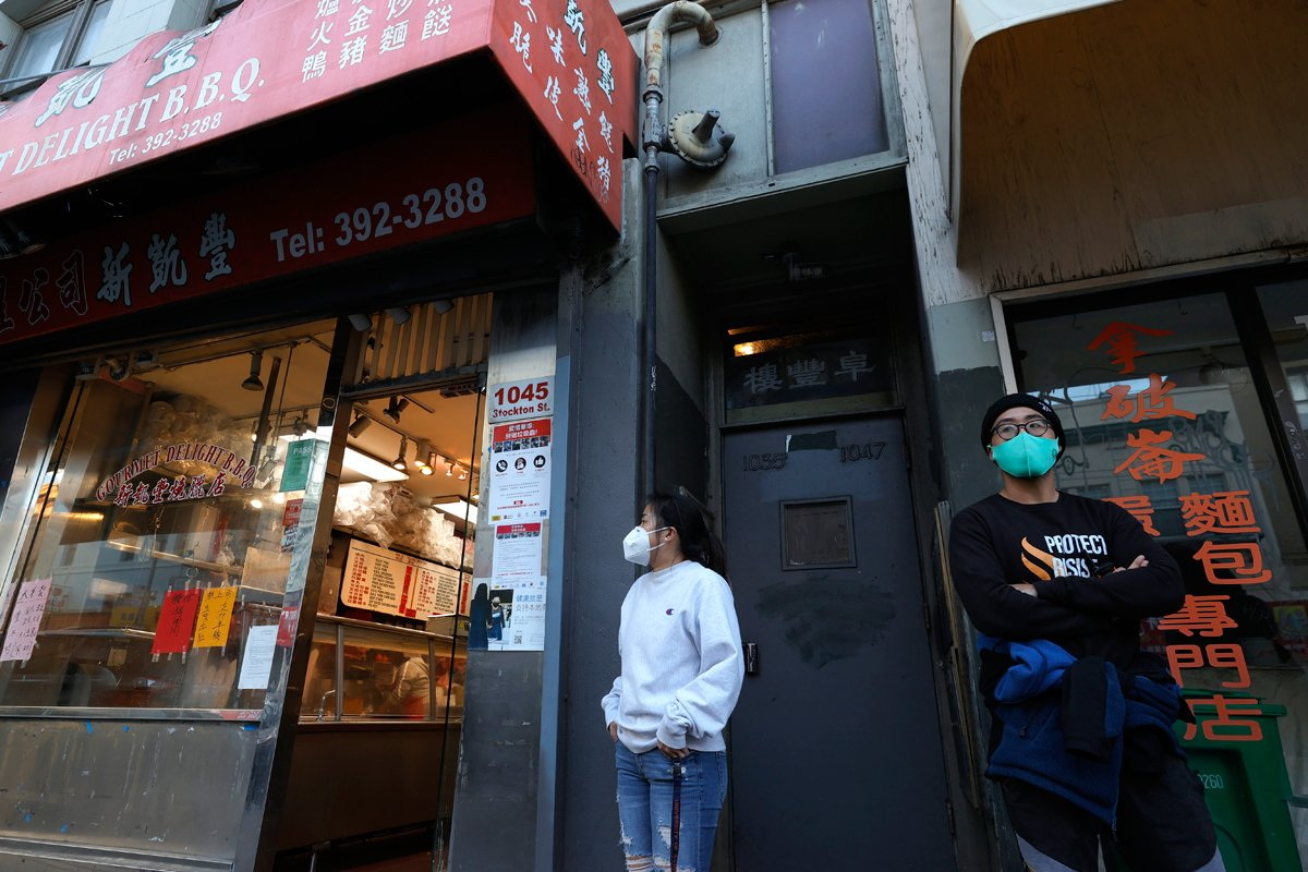 two asian americans wait outside a restaurant in Chinatown, San Francisco