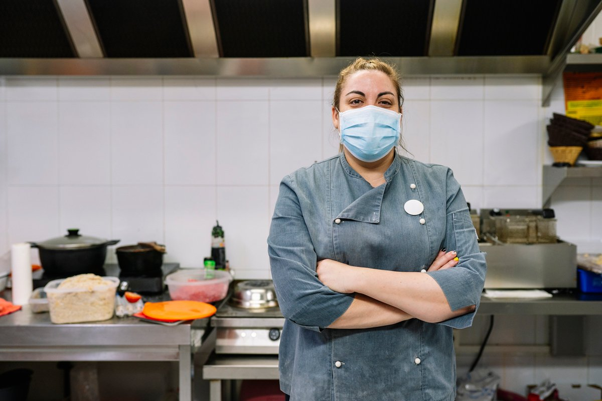 A woman chef stands in her new york city restaurant wearing a mask during the covid pandemic