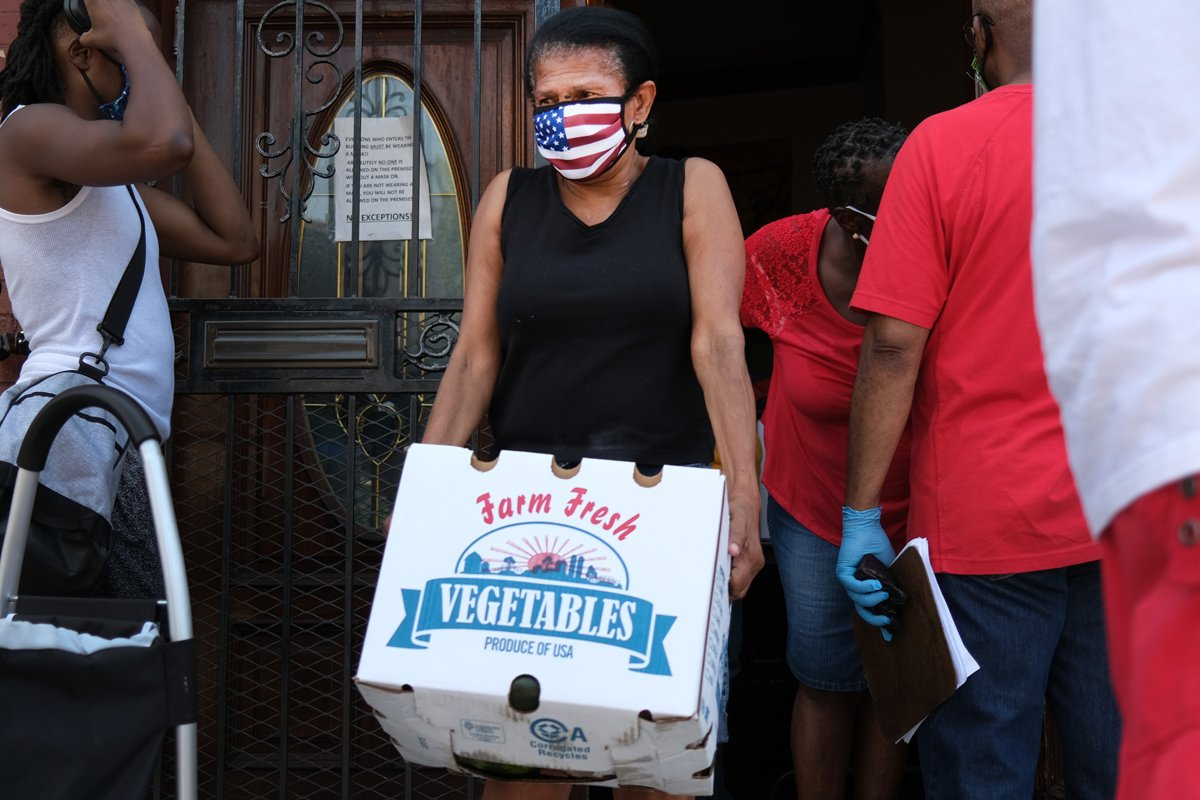 Food is distributed at the Ebenezer Seventh-day Adventist church on July 22, 2020 in the Brooklyn borough of New York City. The church distributes hundreds of packages of food every Wednesday. While many New York neighborhoods have long depended on charities, food banks and nonprofits to meet their nutritional needs, the Covid-19 pandemic has only multiplied the number of residents experiencing food insecurity. Across the city groups that serve those in need are seeing a huge increase in clients. According to the mayor's office, an estimated 2 million people are currently food insecure in New York City, which is up from 1 million people before the pandemic. (Photo by Spencer Platt/Getty Images)
