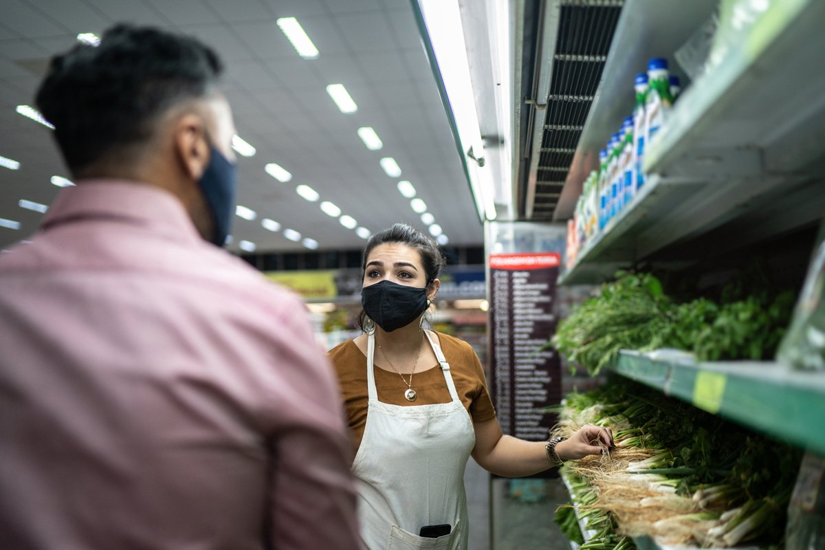 a dietician helps a shopper pick the healthiest food at a supermarket