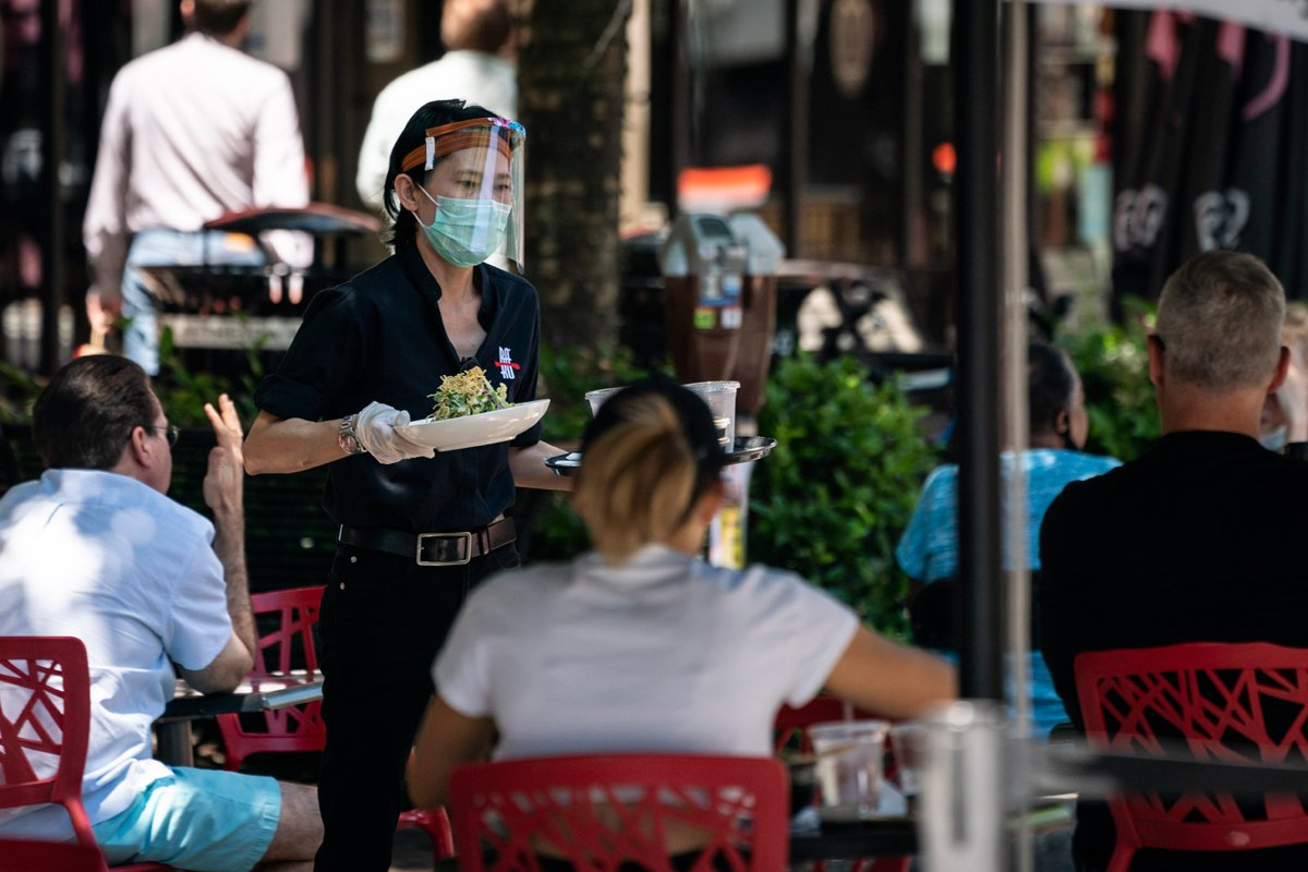 A waiter at Raku, an Asian restaurant in Bethesda, wears a protective face mask as serve customers outdoors amid the coronavirus pandemic on June 12, 2020 in Bethesda, Maryland. (Photo by Sarah Silbiger/Getty Images)