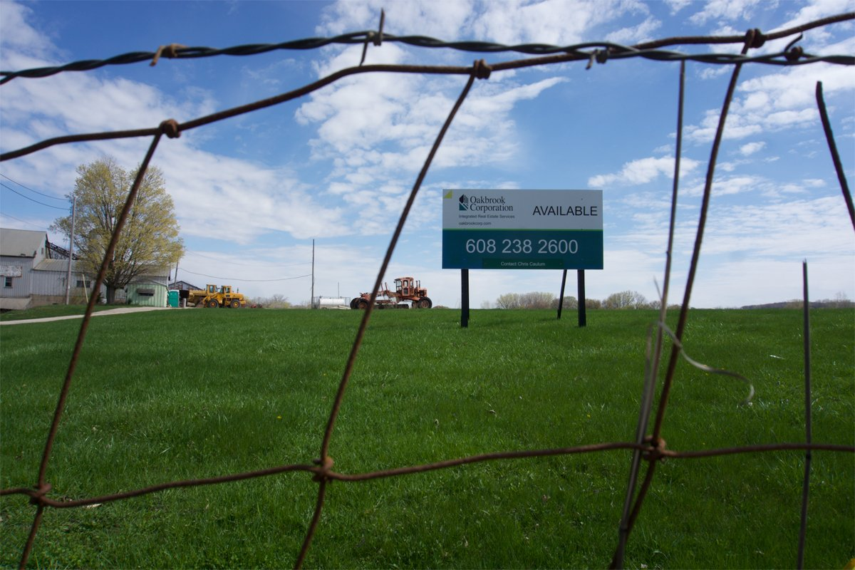 A view of the Voit farm in Wisconsin through a barbed wire fence. (Photo by Susan Shain)