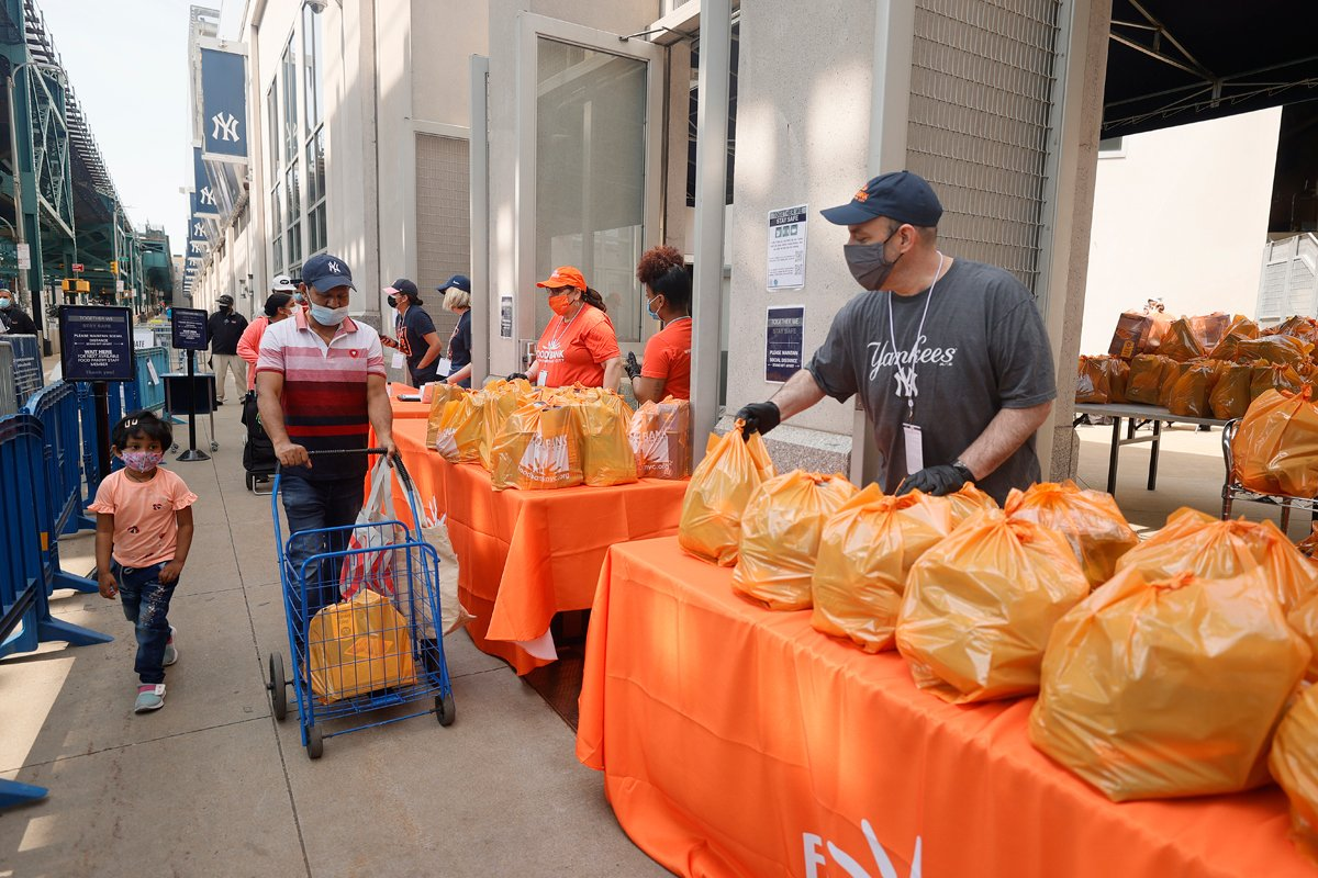 A young child watches as local residents receive food items as Food Bank For New York City teams up with the New York Yankees to kick-off monthly food distribution for New Yorkers in need at Yankee Stadium on May 20, 2021 in New York City.