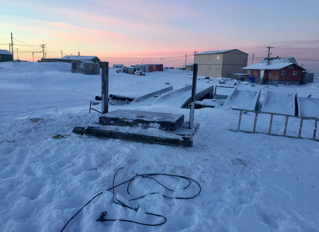 Sunset over an ice cellar. looking up from an iñupiat ice cellar. (Photo courtesy of Qaiyaan Harcharek)