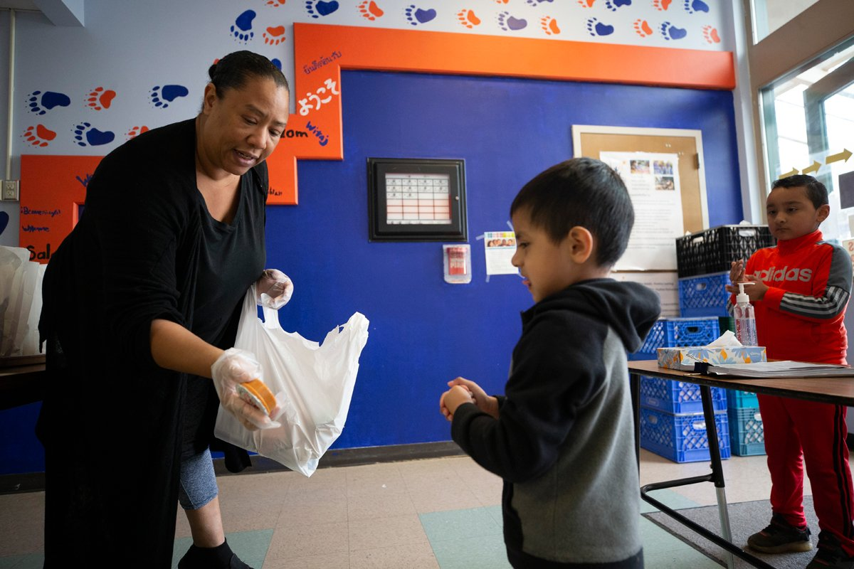 a lady hands a student a school meal