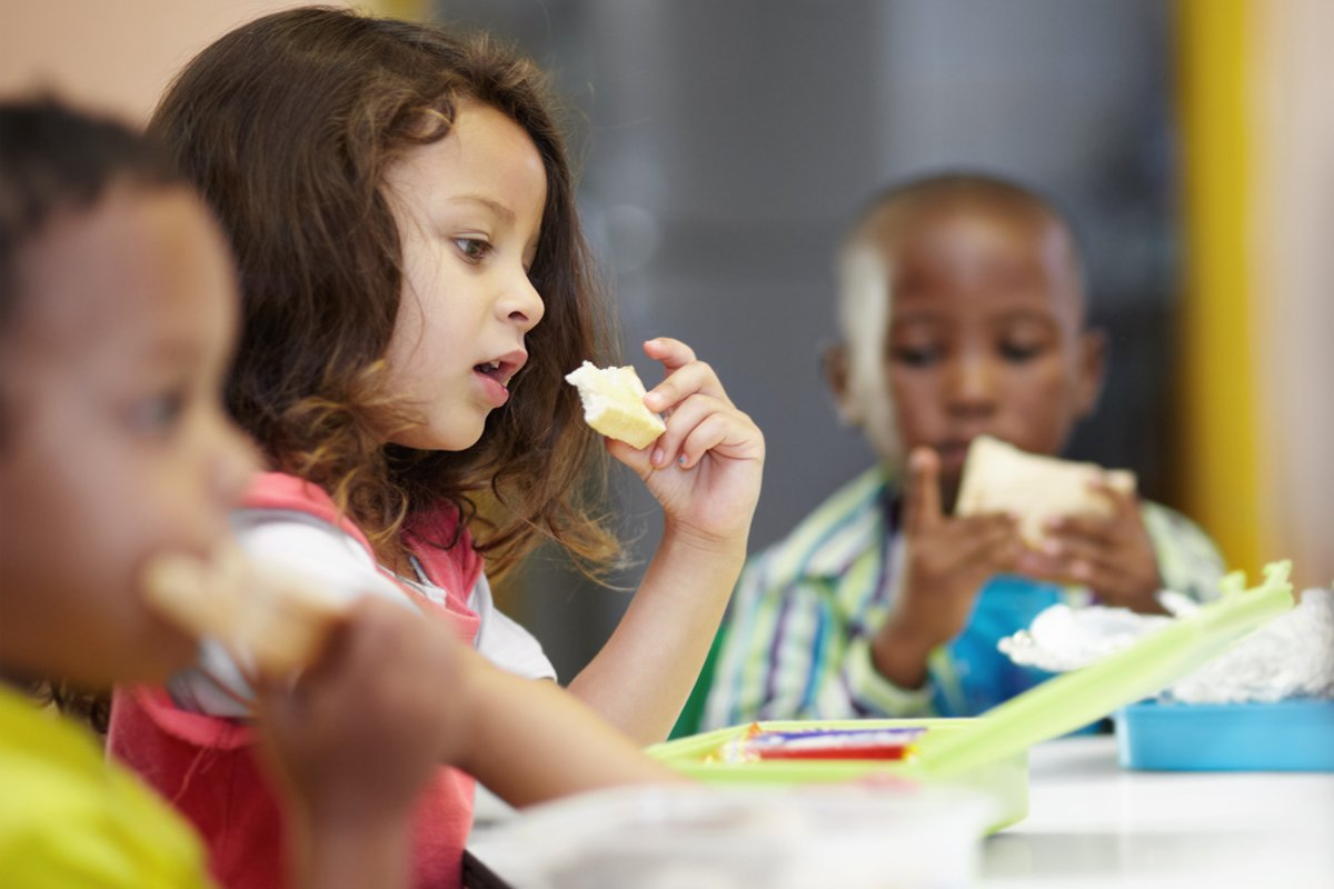 three children eating federally subsidized school meals