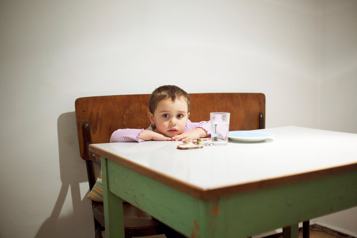 a hungry child sits at a table with just a tiny amount of food looking a little bit haunted