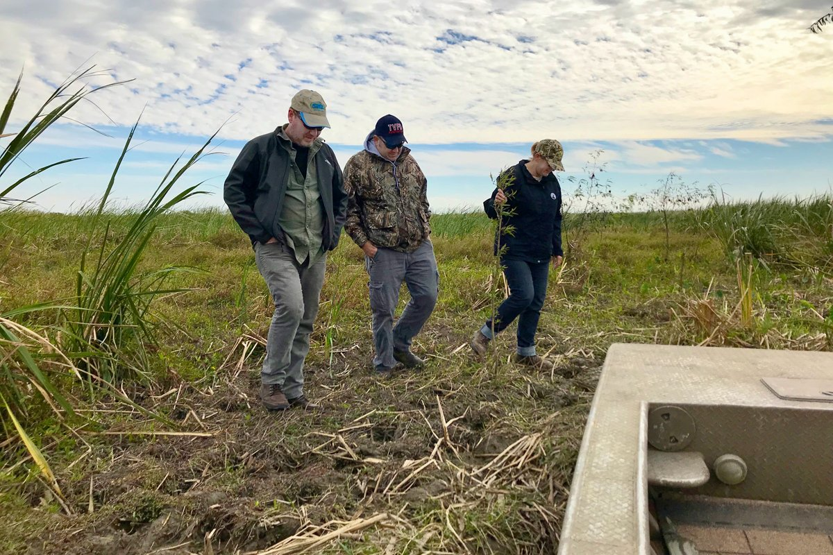 Chef Dana Honn (left) and others walking on new land created as part of a Gulf restoration project. (Photo courtesy of the National Wildlife Federation)