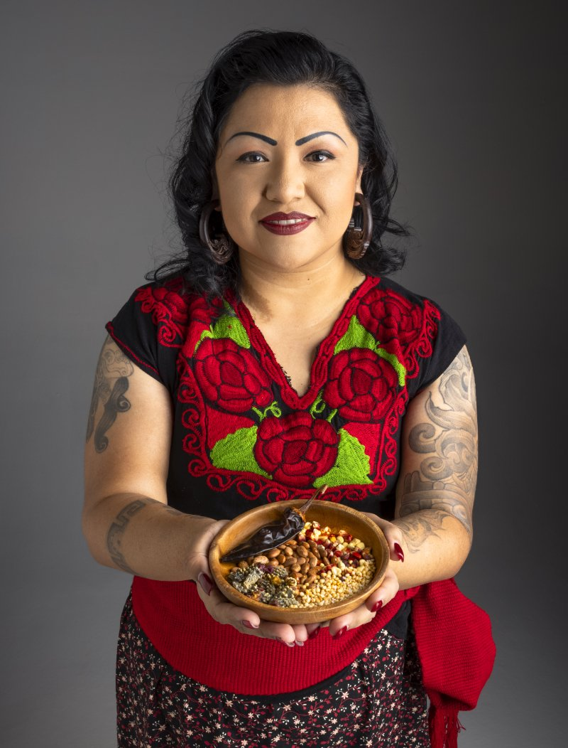 Maria Parra Cano holding a bowl of indigenous foods