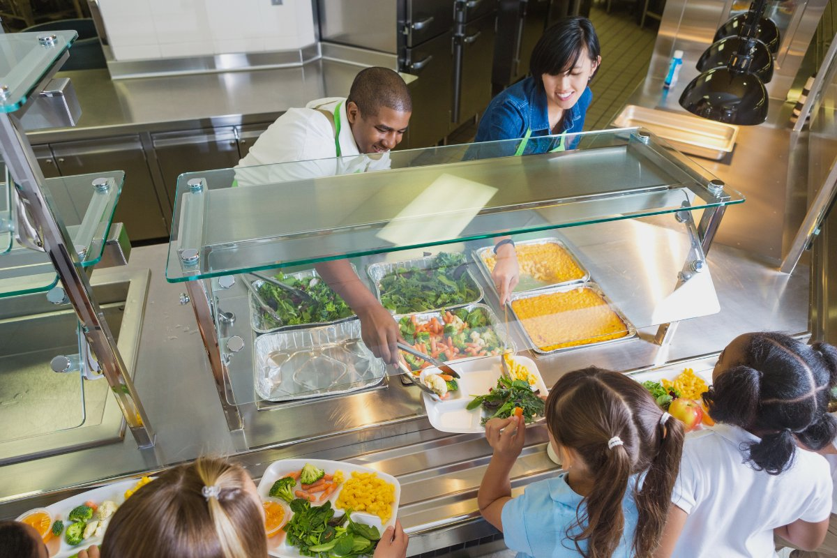 cafeteria workers serve farm to school produce to students to improve their nutrition and support local farmers