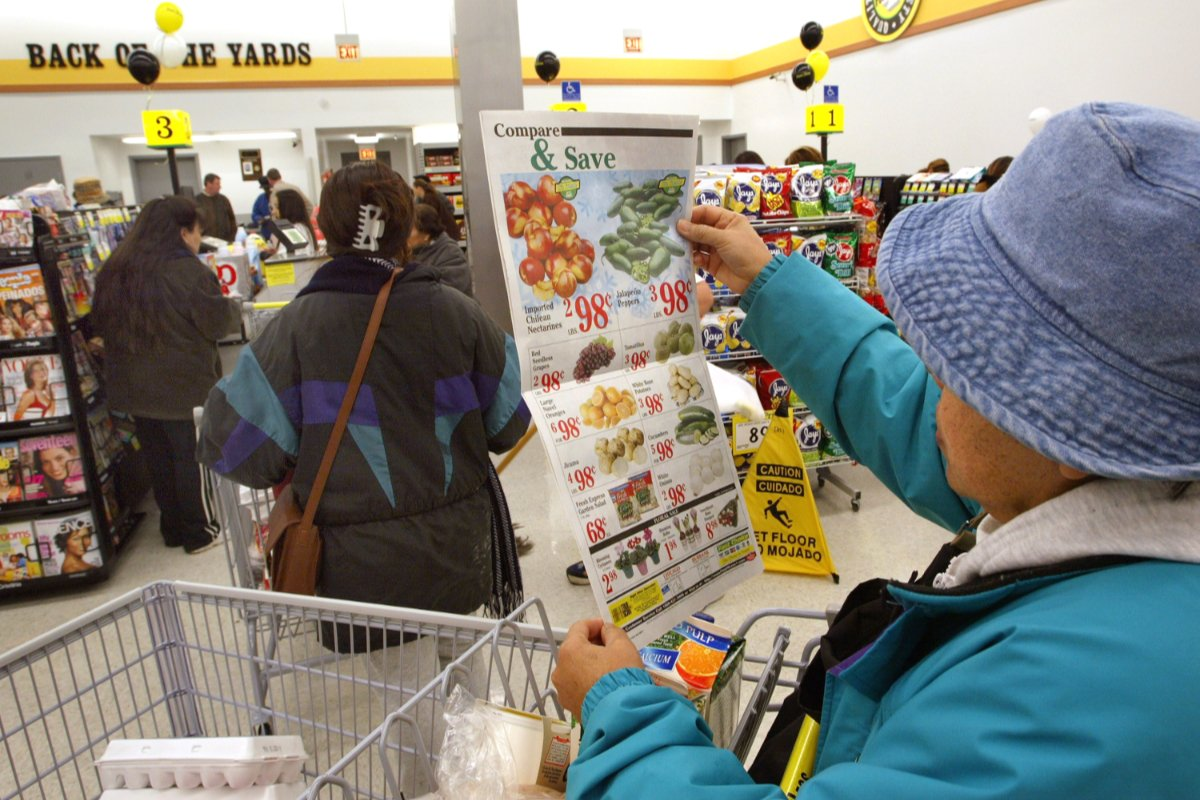 A grocery shopper looks at a list of discounts and prices inside a supermarket. Those prices do not reflect a true cost accounting of food.