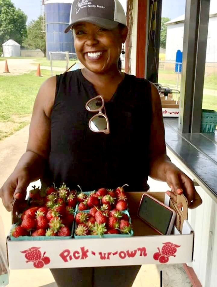 Illinois State Representative Sonya Harper holding a flat of pick-your-own strawberries.