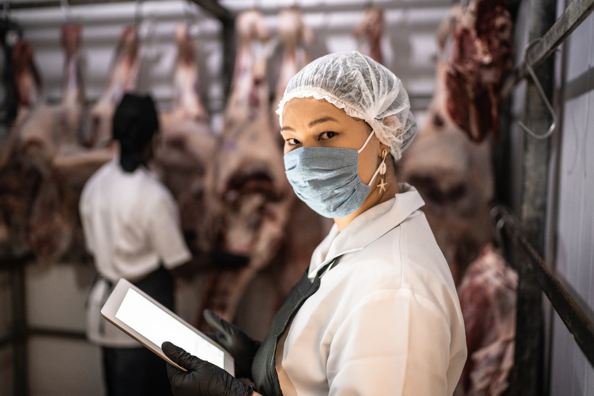 Portrait of female butcher using digital tablet with face mask at a meatpacking plant