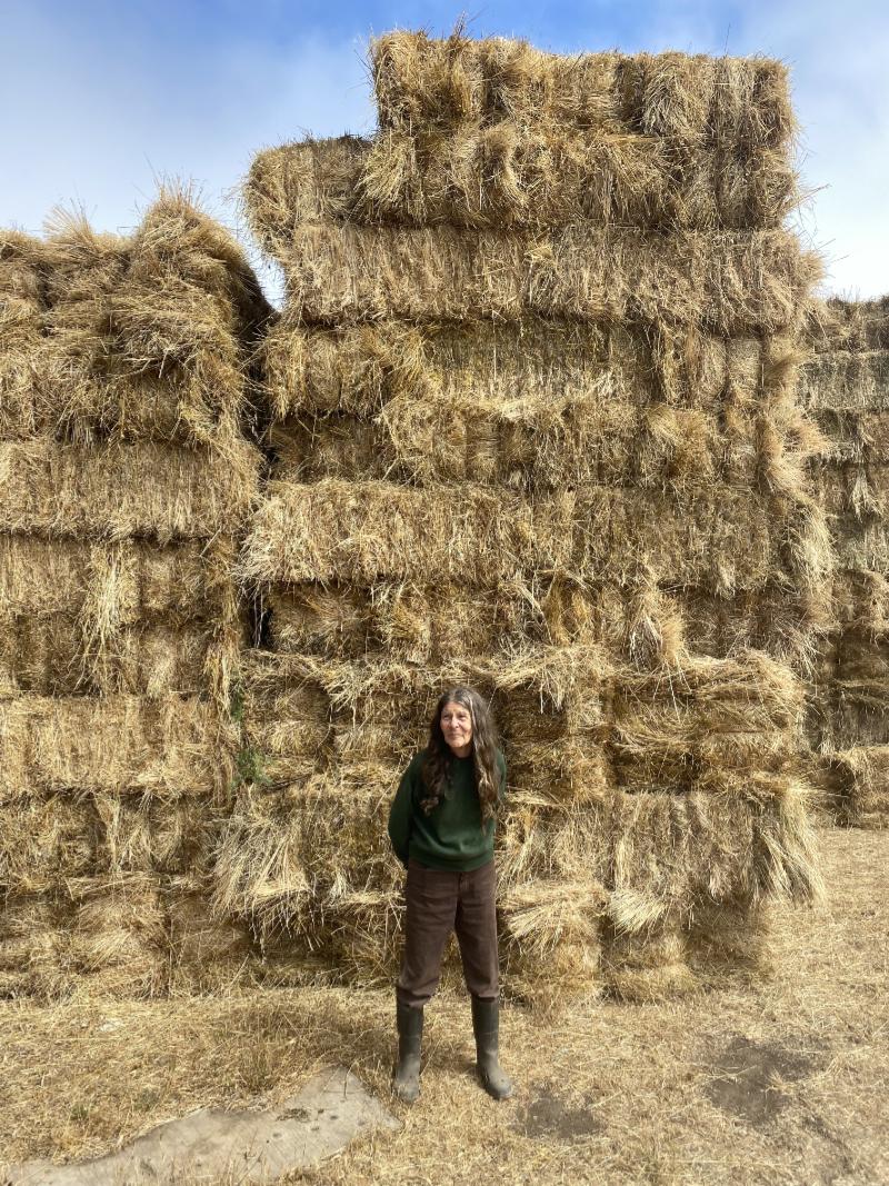 Hazel Flett stands in front of a huge pile of hay bales. (Photo credit: Judy Starkman / Mizzica Films)