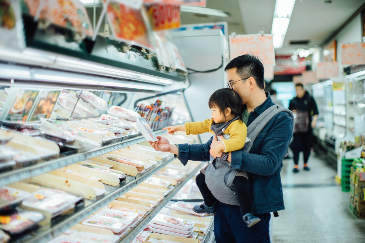 Young Asian father grocery shopping with cute little daughter in supermarket, they are shopping for fresh meat