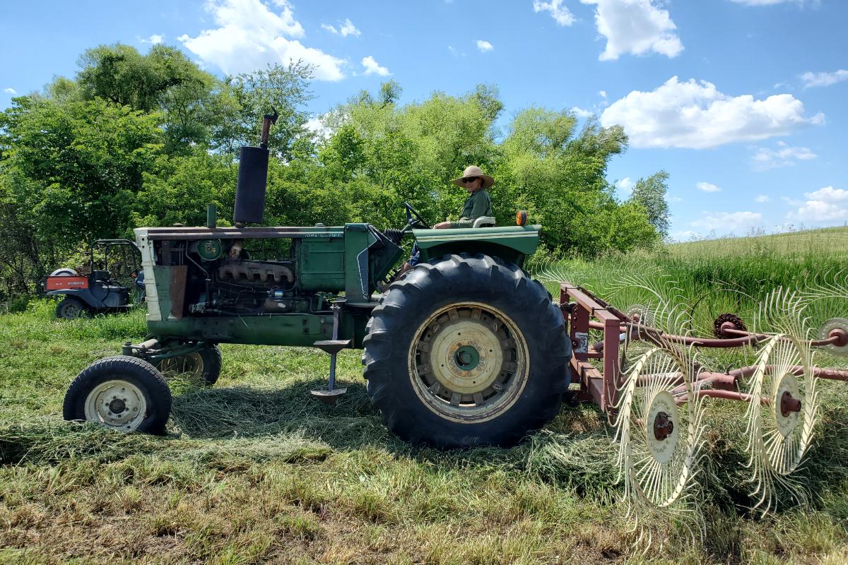 Beth Hoffman raking hay on her tractor.