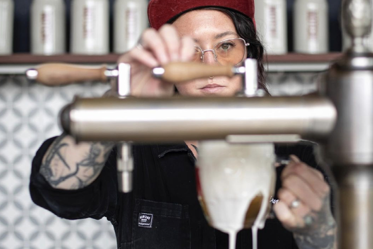 Brienne Allan pouring a beer at notch brewery. (Photograph by Iaritza Menjivar, provided by Brienne Allan)
